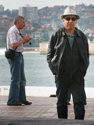 Paul walking around unnoticed, guy behind him doesn't know where the attraction is.