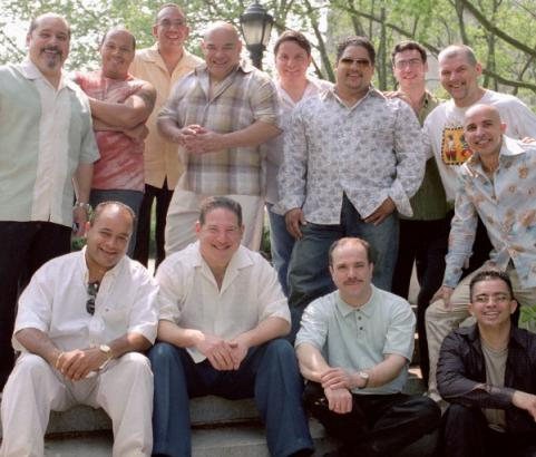 Oscar Hernández (sitting 3rd from the left) is the founder, director and pianist from the Spanish Harlem Orchestra and was the arranger and producer of The Capeman.